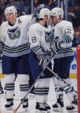 Glen Wesley, Geoff Sanderson, and Steven Rice celebrate a goal