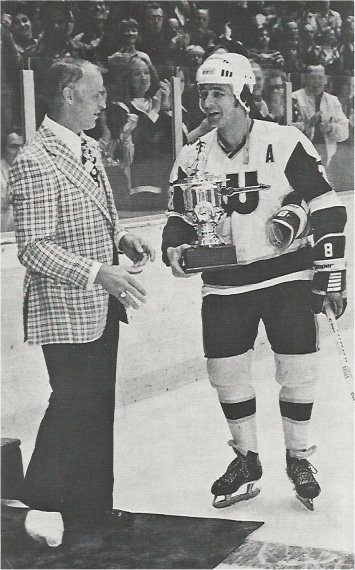 Tom Webster receives an award for recording his 200th WHA goal from an injured Gordie Howe